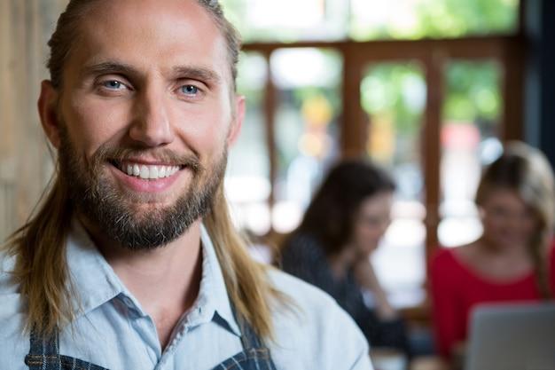 Retrato de barista masculino confiante com clientes do sexo feminino em segundo plano em uma cafeteria