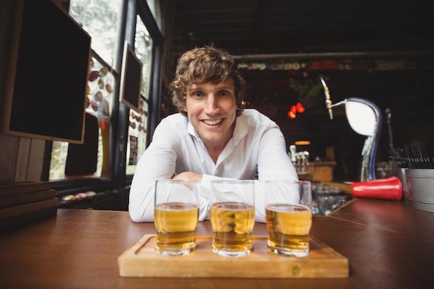 Retrato de barman com bandeja de copos de uísque no balcão de bar