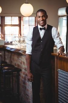Retrato de barman em pé no balcão de bar