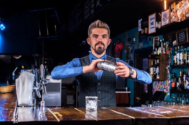 Retrato de barman fazendo coquetel na boate