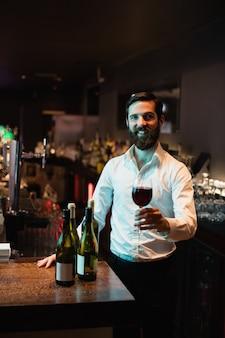 Retrato, de, barman, segurando, copo vinho tinto
