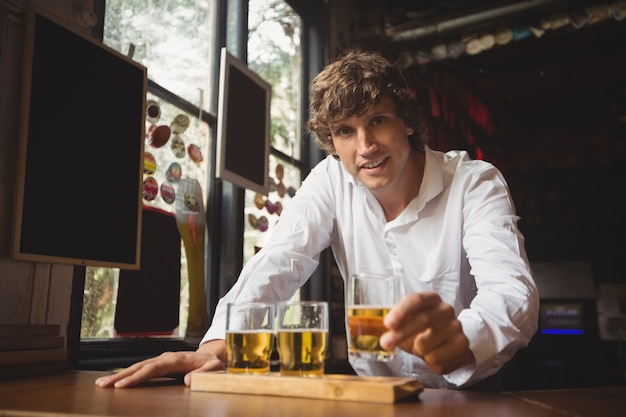 Retrato de barman, segurando o copo de uísque no balcão de bar