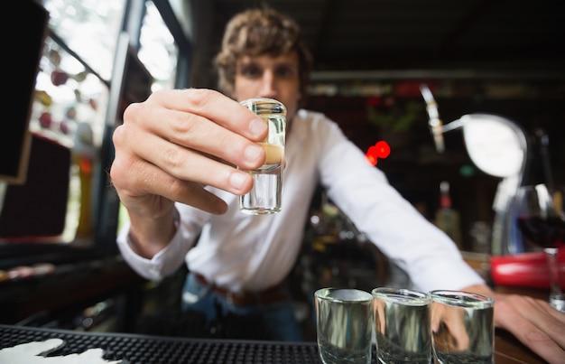 Retrato de barman segurando tequila copo no balcão de bar