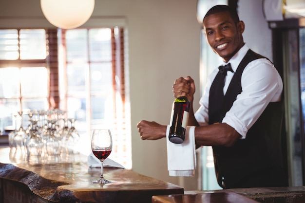 Retrato de barman segurando uma garrafa de vinho