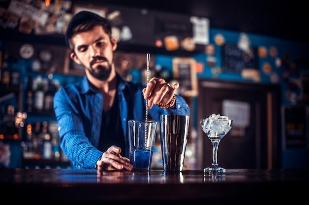 Retrato de barman servindo bebida alcoólica fresca nos copos, enquanto estava perto do balcão do bar
