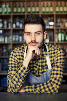Retrato de bartender confiante no balcão do bar