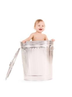 Retrato de bebê adorável na lata de lixo