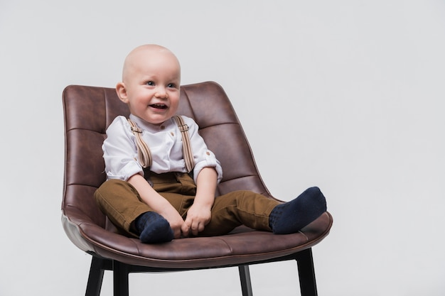 Retrato de bebê adorável, sentado em uma cadeira