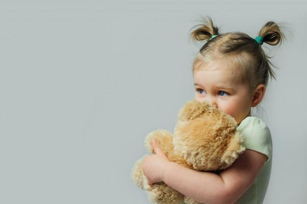 Retrato de bebê criança segurando o brinquedo macio, olhando para longe