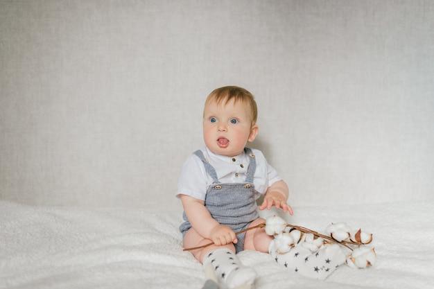 Retrato de bebê engraçado sentado na cama branca no quarto.