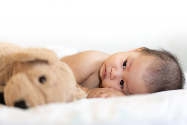 Retrato de bebê feliz relaxante na cama
