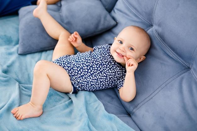 Retrato de bebê feliz rindo com olhos azuis, camisa azul, sentado no sofá.