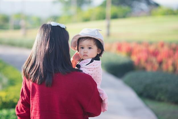 Retrato de bebê fofo e a mãe dela viajam no jardim de flores