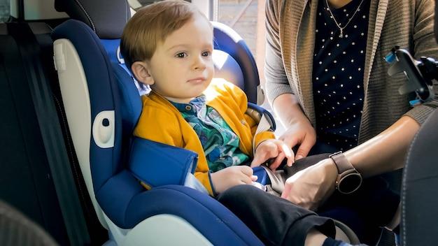 Retrato de bebê fofo sentado na cadeira de segurança do carro.