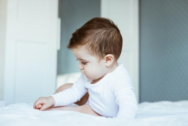 Retrato de bebê menino criança em bodysuit branco na cama no quarto. visão lateral do conceito de infância feliz