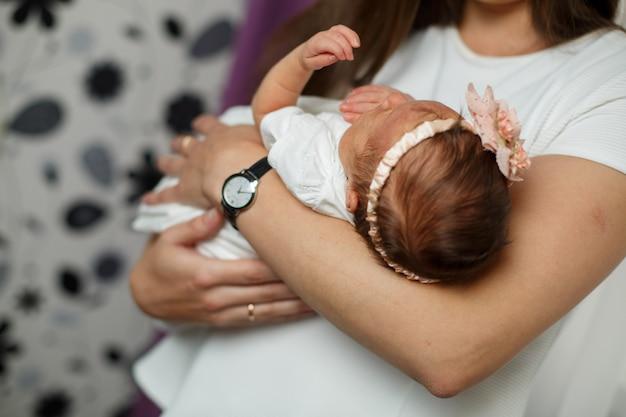 Retrato de bebê recém-nascido com a mãe nos braços. menina recém-nascida nas mãos de sua mãe.