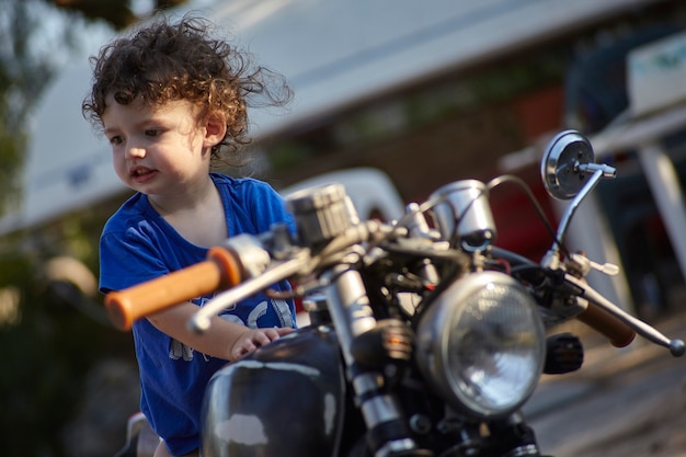 Retrato de bebê sentado em uma velha motocicleta feliz e sorridente