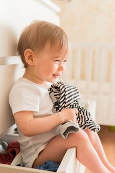 Retrato de bebê sentado na gaveta