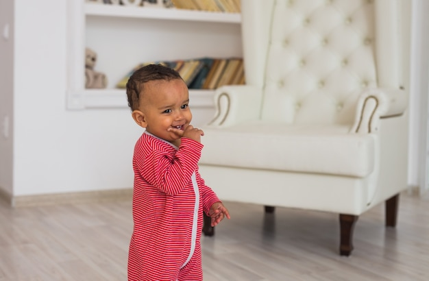 Retrato de bebê sorridente de raça mista em casa.