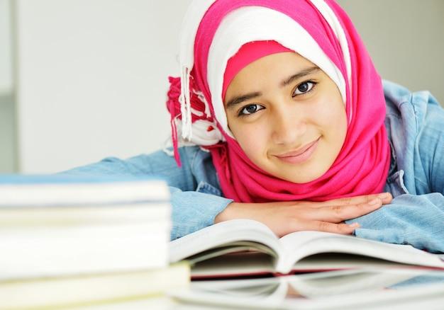 Retrato de bela menina muçulmana árabe com livros