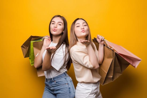 Retrato de belas garotas atraentes carregando sacolas coloridas enviando beijo no ar se divertindo isolado em uma parede de cor amarela vibrante de brilho vívido brilhante