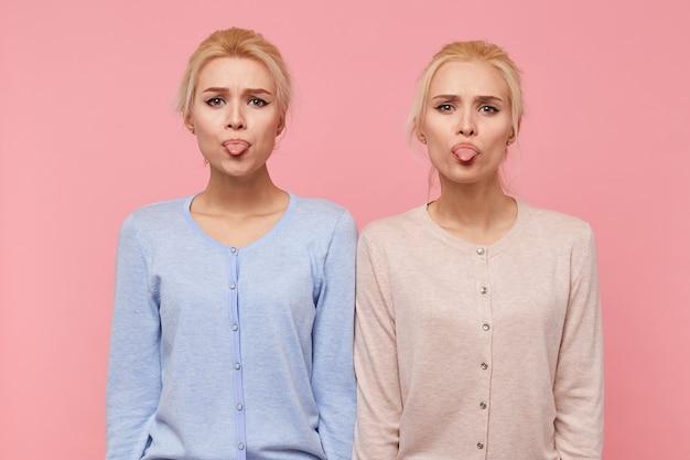 Retrato de belas jovens loiras gêmeas fazem caretas e mostram línguas, olhando para a câmera isolada sobre fundo rosa.