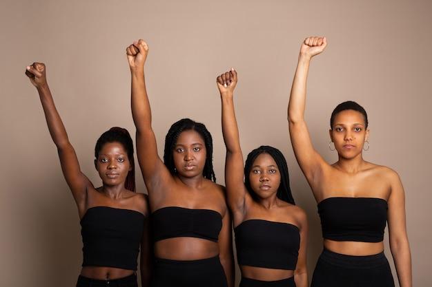 Retrato de belas jovens mulheres africanas com os braços levantados