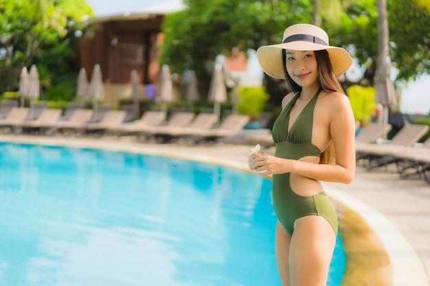 Retrato de belas mulheres asiáticas sorriso feliz relaxar ao redor da piscina no hotel resort