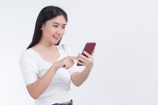 Retrato de belas mulheres asiáticas use o telefone celular alegremente em uma parede branca