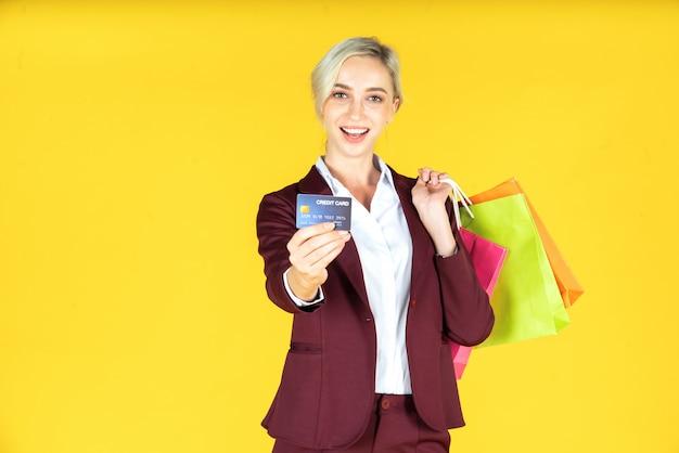 Retrato de belas mulheres segurando sacolas com cartão de crédito e desfrutar de compras em amarelo