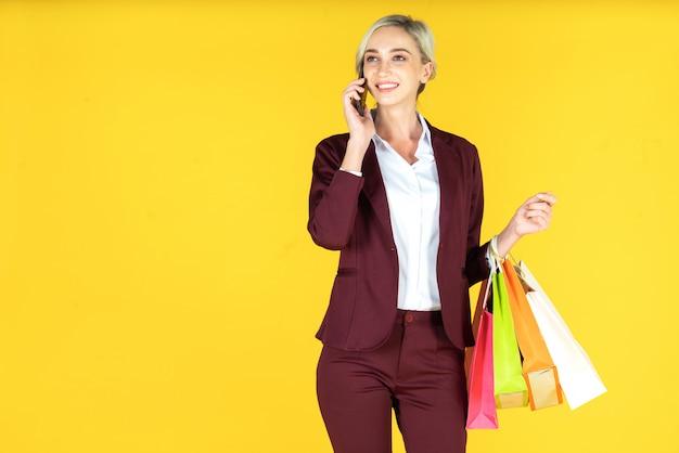 Retrato de belas mulheres segurando sacolas de compras e desfrutar de compras em amarelo
