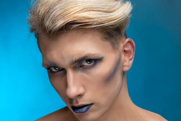 Retrato de beleza close-up de um jovem com maquiagem profissional e cabelo loiro voador