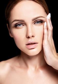 Retrato de beleza closeup glamour do modelo sensual caucasiano mulher jovem e bonita com maquiagem nude, tocando sua pele limpa perfeita posando no escuro