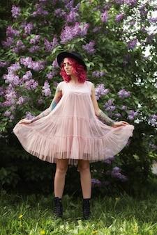 Retrato de beleza de primavera de uma linda garota com cabelo vermelho nos galhos de uma flor lilás.