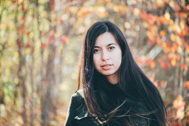 Retrato de beleza feminina rodeado por folhagem vívida.