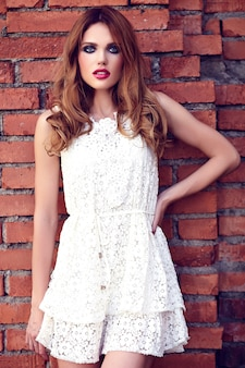 Retrato de beleza glamour do modelo sensual caucasiano mulher jovem e bonita com maquiagem de noite no vestido branco de verão posando na rua perto da parede de tijolo