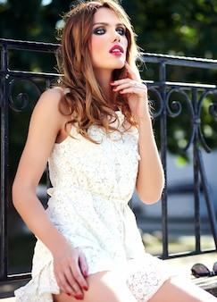 Retrato de beleza glamour do modelo sensual caucasiano mulher jovem e bonita com maquiagem de noite no vestido branco do verão posando na rua