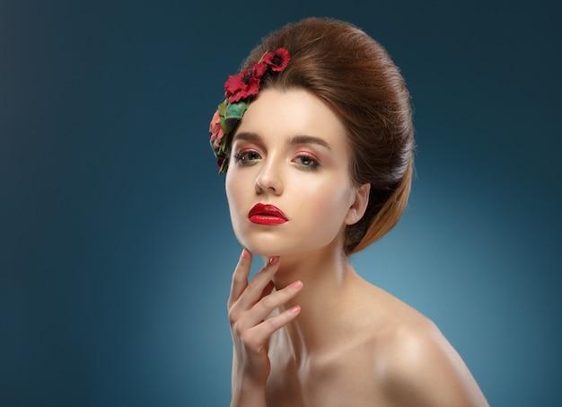Retrato de beleza. mulher tocando seu rosto. mulher bonita com maquiagem colorida e flores no cabelo