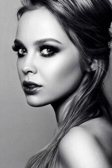 Retrato de beleza preto e branco de jovem olhando por cima do ombro. pele perfeita e maquiagem olhos esfumados.