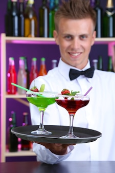Retrato de belo barman com coquetéis diferentes, no bar