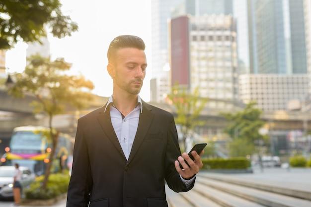 Retrato de belo jovem empresário italiano ao ar livre na cidade, vestindo terno