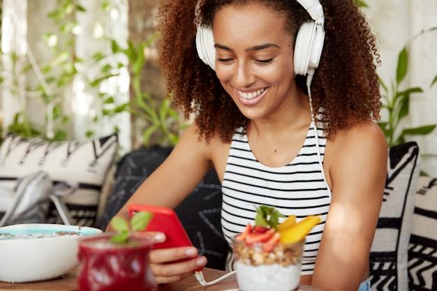Retrato de blogueira ouve música em fones de ouvido modernos, usa smartphone para instalar novo aplicativo, usa internet grátis enquanto se regozija em uma cafeteria com um saboroso smoothie e coquetel