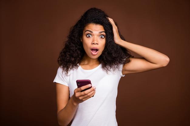 Retrato de blogueiro de garota afro americana espantado usar telefone celular ler informações olhar estupor mão tocar cabeça gritar omg usar roupa de estilo casual.