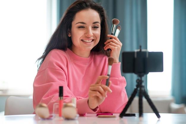 Retrato de blogueiro gravando vídeo com acessórios de maquiagem