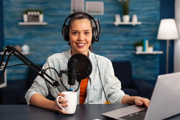 Retrato de blogueiro sorridente, olhando para a câmera antes de iniciar o vídeo ao vivo no podcast de estúdio caseiro segurando uma xícara de café. mulher blogueira criadora de conteúdo gravando transmissão ao vivo de brodcast para internet