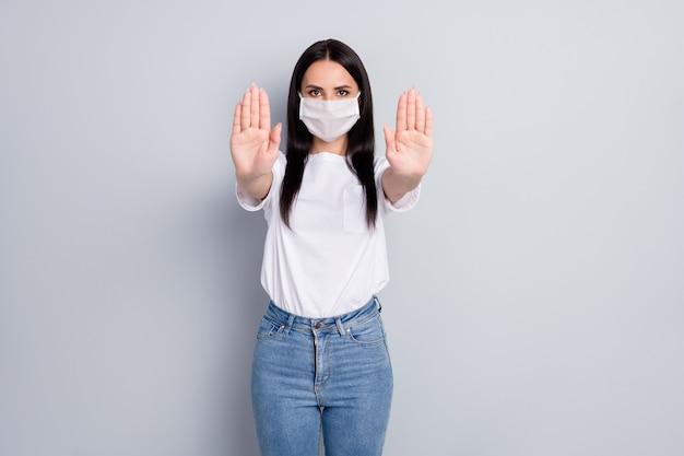 Retrato de bom conteúdo atraente garota séria de cabelos retos mostrando sinal de parada solução saúde quarentena medida contato lavar as mãos isoladas em um fundo cinza claro