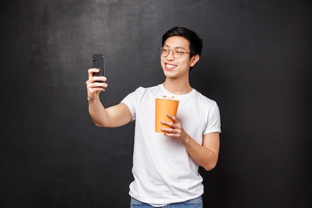 Retrato de bonito alegre jovem asiático masculino blogueiro gravar vídeo dele comendo pipoca