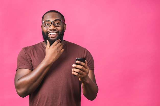Retrato de bonito animado alegre alegre delicioso afro-americano negro vestindo casual, enviando e recebendo mensagens para sua amante isolada sobre fundo rosa. usando o telefone.