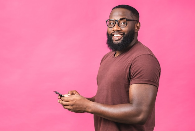 Retrato de bonito animado alegre alegre delicioso afro-americano vestindo casual, enviando e recebendo mensagens para sua amante isolada contra o fundo rosa. usando o telefone.