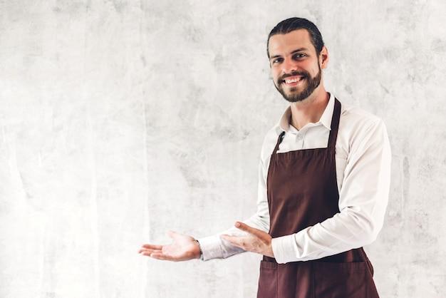 Retrato de bonito barista barbudo homem pequeno empresário sorrindo na parede